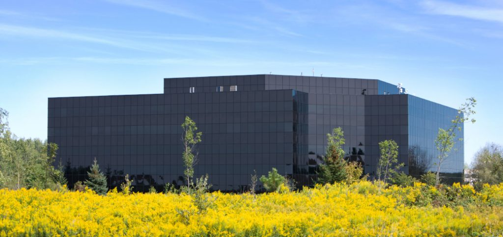 Black glazed building with field of yellow flowers in foreground and blue sky in background.