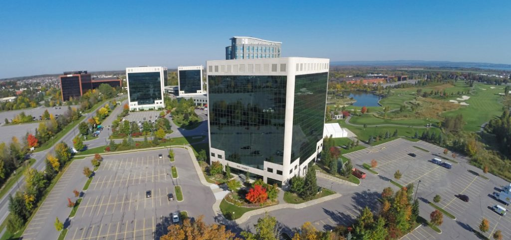 Aerial view of four office towers with parking lots below and pond in background on solid blue sky.