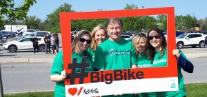 Four people in green shirts standing outdoors behind a red Big Bike picture frame.