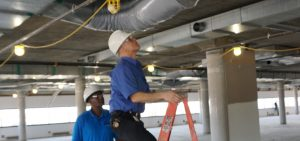 Two men in hardhats looking at HVAC system in indoor office space.