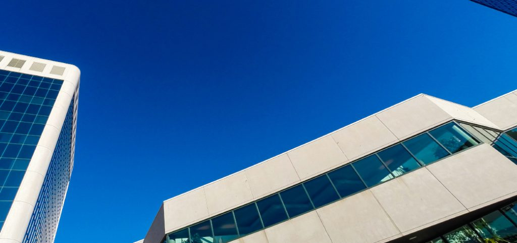 View looking up at concrete panel-clad buildings with solid blue sky in background