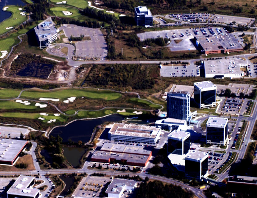 Aerial view of office towers next to golf course.