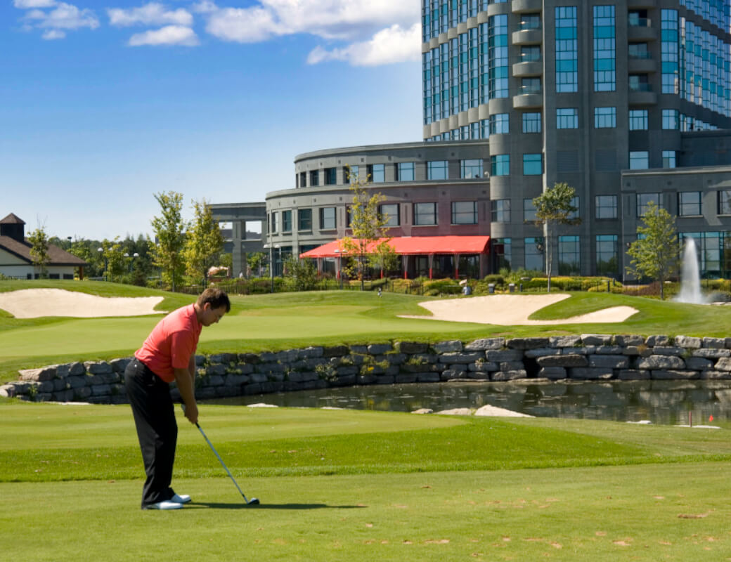 Man in red shirt putting with hotel in background.