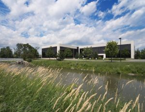 Lowrise black glazed office building with creek and cattails in foreground agains cloudy and blue sky.